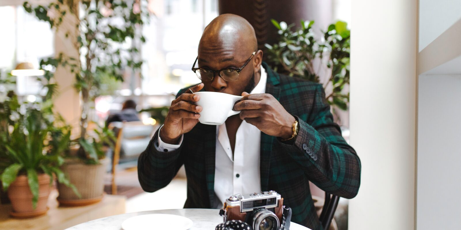 a bald guy in a suit drinking coffee in a coffeeshop with plants