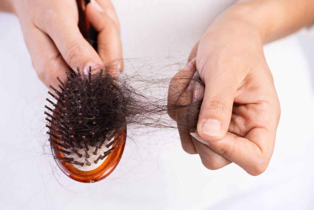 a hair brush with hair strands from hair loss