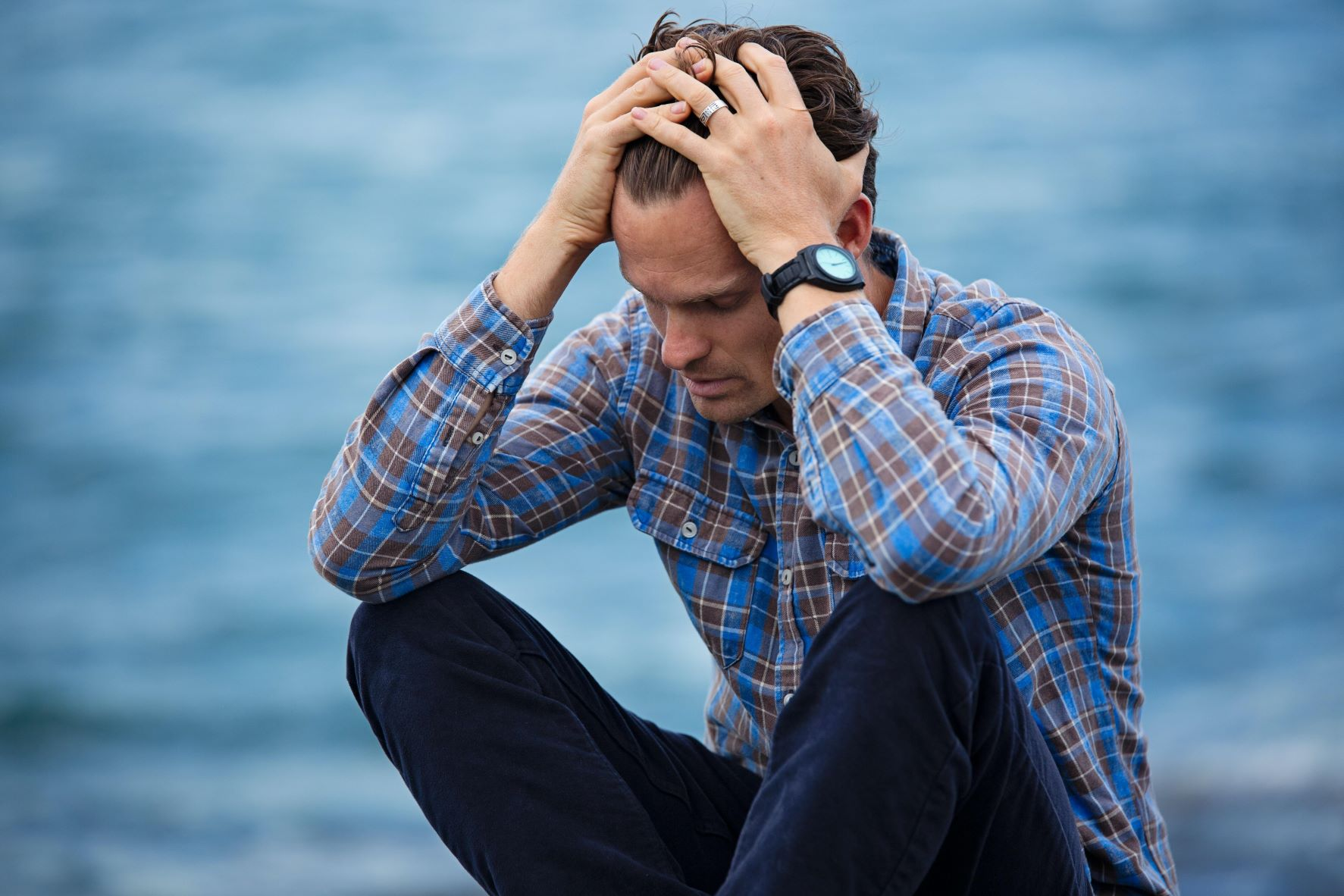 a guy sitting at the beach looking stressed
