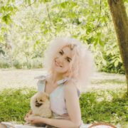 a woman with bleached hair holding a dog in a park