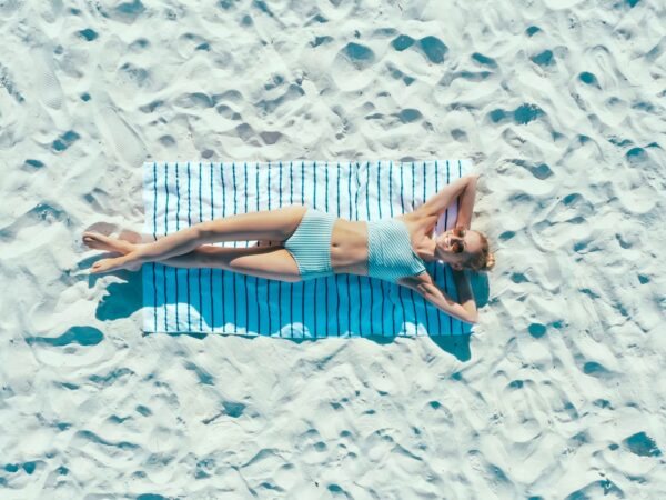 a woman tanning under the sun with sand how long does it take to tan